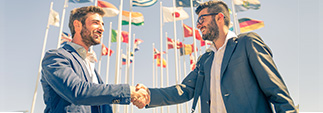 Two business people shaking hands in-front of international flags