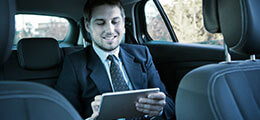 Business man in a taxi checking email on a tablet